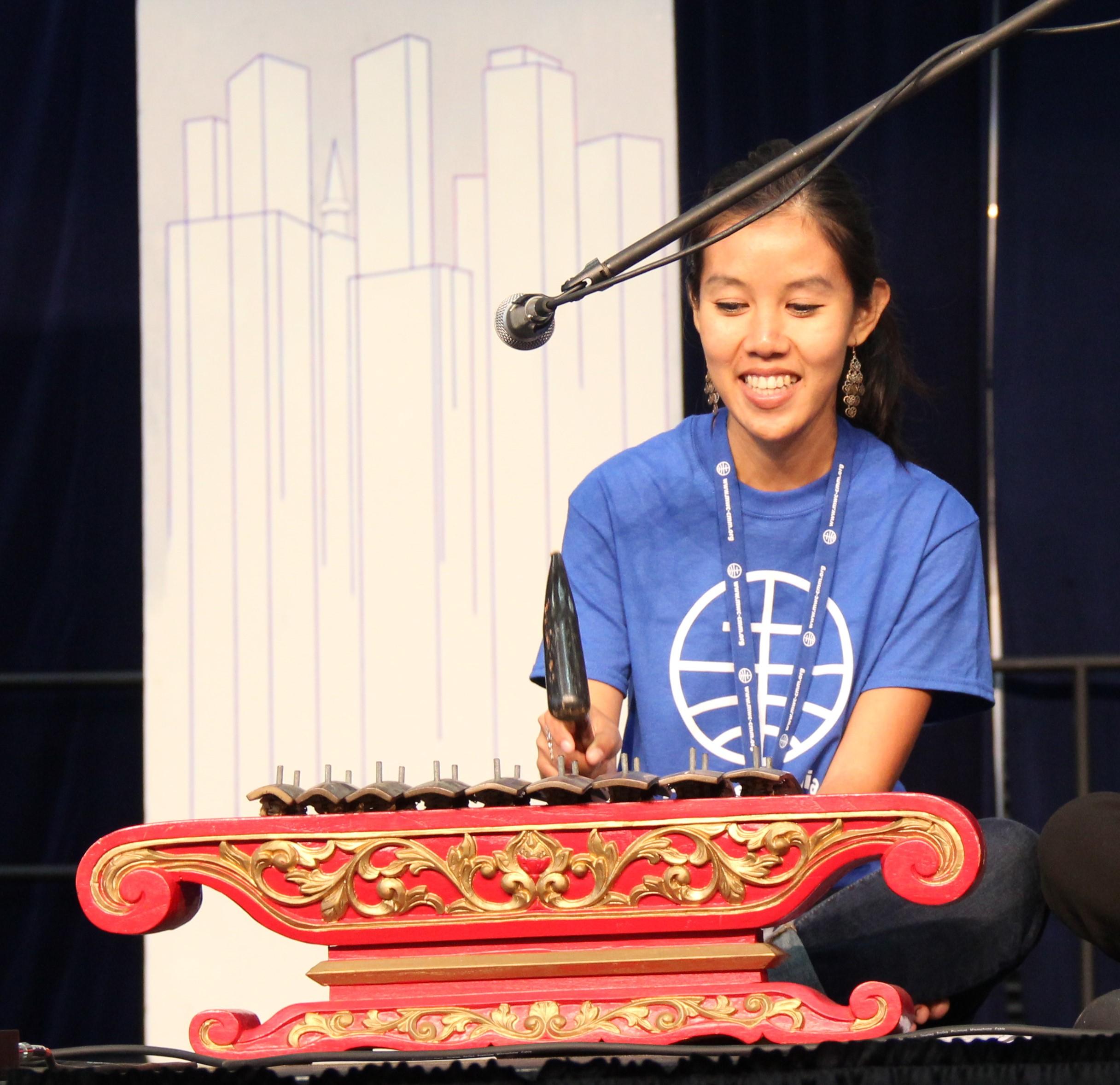 woman plays indonesian gamelan instrument