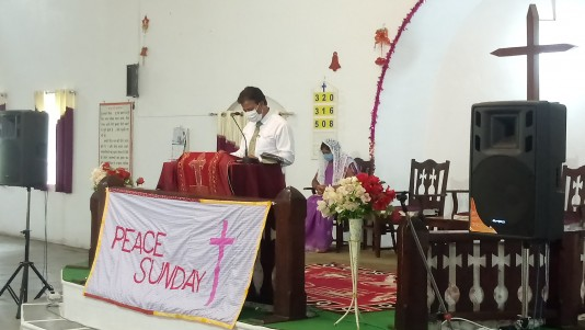 masked preacher in church with peace Sunday banner