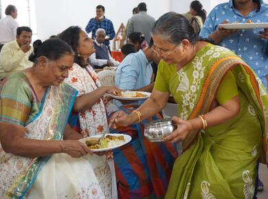 two women in colourful saris serve each other food