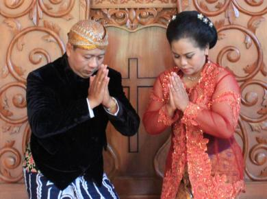 Reverend Budi Santoso with his wife in traditional costumes, beskap (for men) and kebaya (for women)