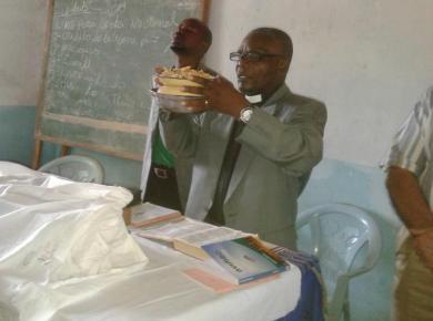 <p>Evangelist Laston Bissani prays for the Communion bread. Photo: courtesy of Laston Bissani.</p>