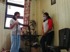two masked women stand socially distanced while discussing