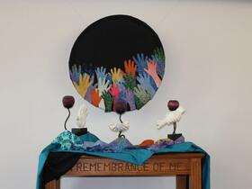 raised hands artwork with dove sculptures