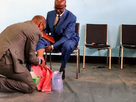 Outgoing MKC President Tewodros Beyene washes the feet of his successor, Deselagn Abede. Photo: Tom Eshleman/LMC