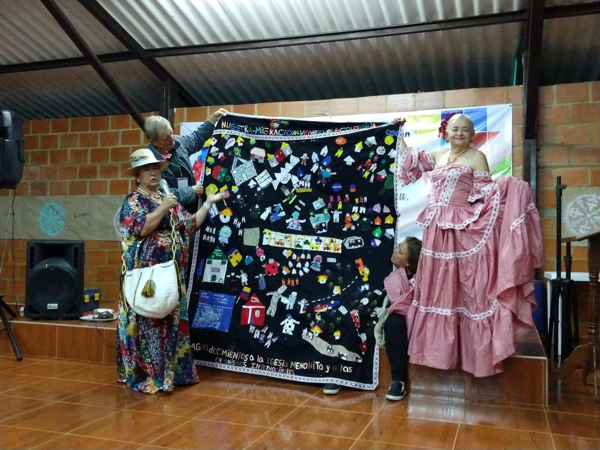 Pastor María de Melo of Iglesia Cristiana Menonita de Riohacha displays a quilt into which Venezuelan refugees have sewed their migration story to process their trauma. Photo: Linda Shelly.