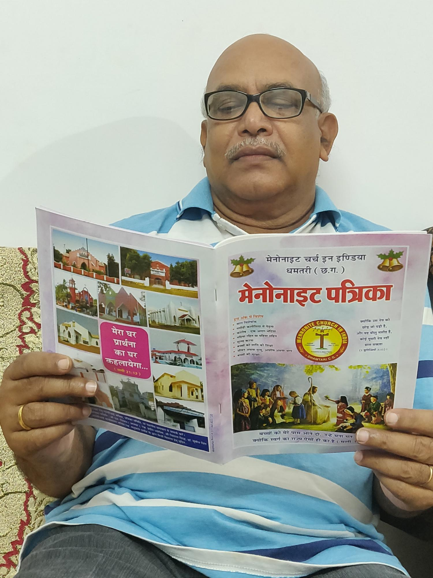 Harendra Milap, member of Mennonite Church Rajnandgaon and the publication committee, reads Mennonait Patrika, a quarterly magazine of Mennonite Church India Dhamtari CG. Photo supplied.