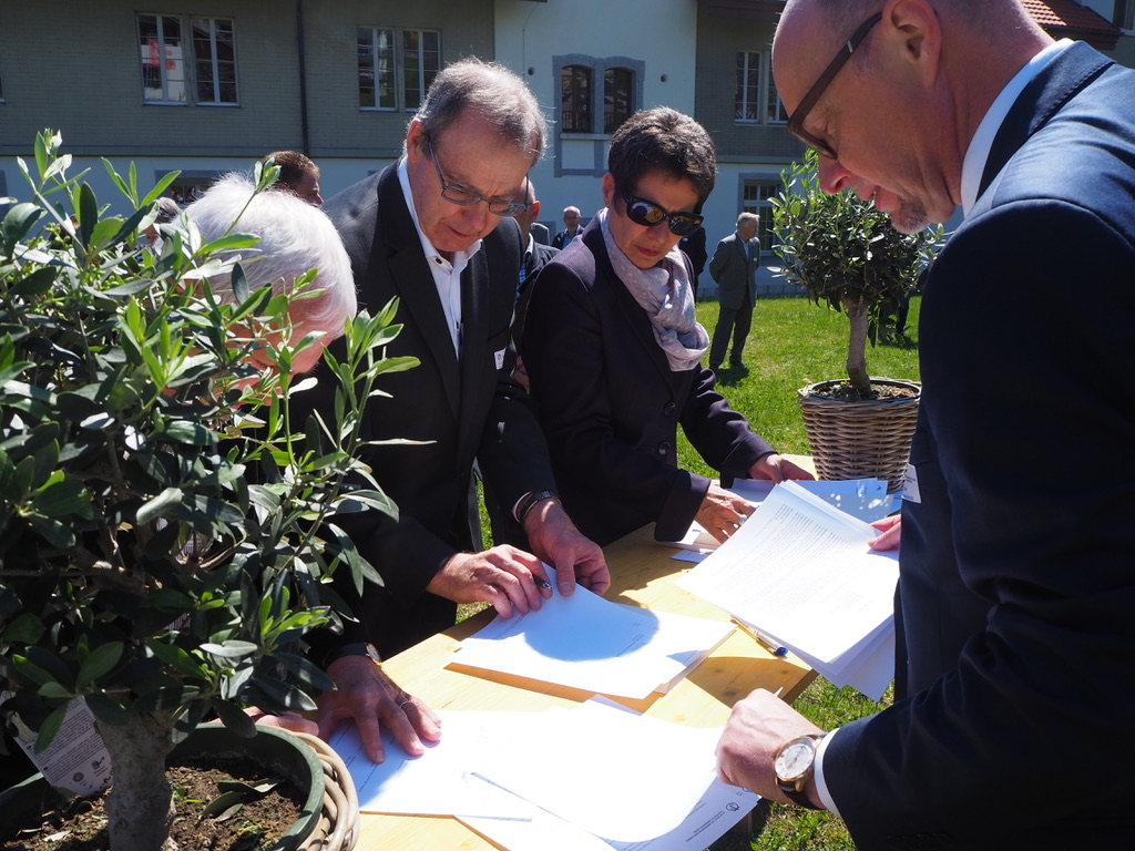 Delegates from KMS/CMS congregations (from left, Karl Martin of Schänzli, Ernest Geiser of Tavannes and Nelly Gerber-Geiser of Sonnenberg) sign a declaration of forgiveness 20 April 2019 as general secretary Jürg Bräker, right, observes. Photo: Raphaël Burkhalter